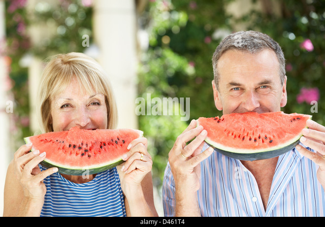 Mother And Adult Daughter Enjoying Slices Of Water Melon - Stock Image
