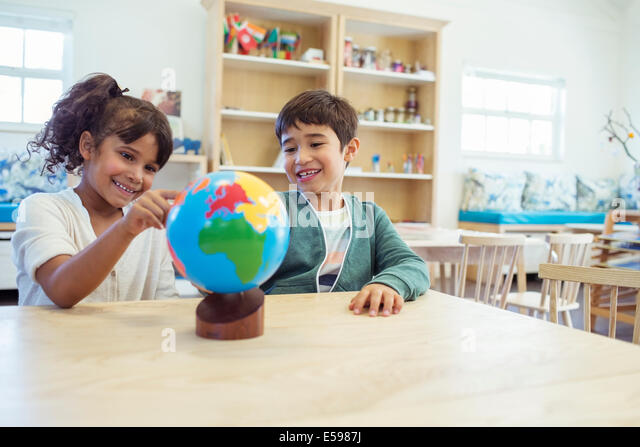 Students examining globe in classroom - Stock Image