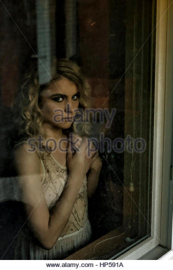 Young woman looking out a window - Stock-Bilder