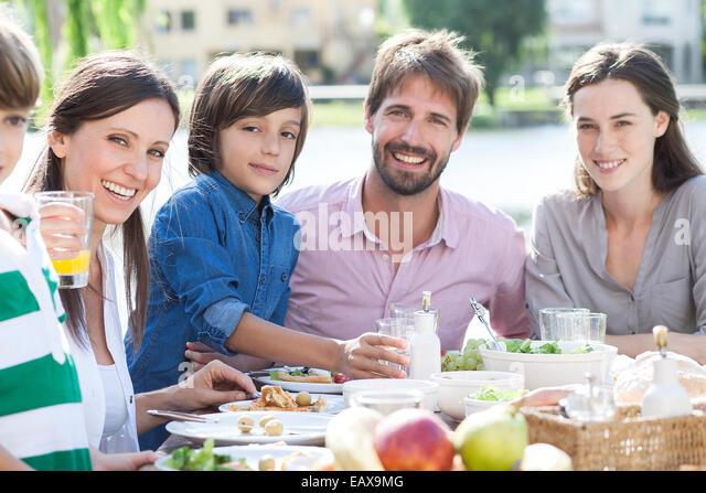 Family eating together outdoors, portrait - Stock-Bilder