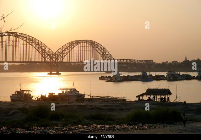 Looking across to the new metal Sagaing bridge silhouetted by the setting sun near Mandalay Myanmar - Stock-Bilder