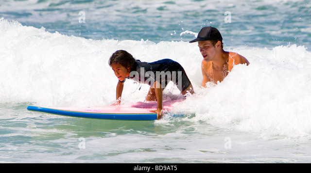 Young girl getting surfing lessons at Surf camp at Del Mar Beach in San Diego County California USA - Stock Image