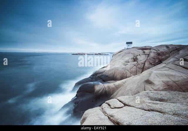Cabin on cliff near sea with dramatic sky - Stock Image