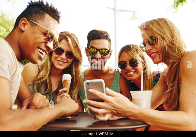 Five adult friends looking at smartphone at park table - Stock-Bilder