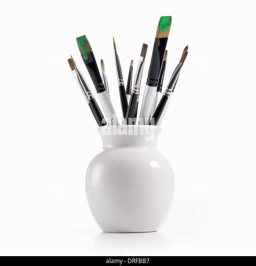 white china pot paintbrushes loaded green paint - Stock Image