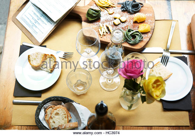 Food and flowers on cafe table. - Stock Image