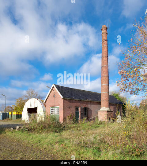 exterior of an old decayed building with brick chimney - Stock Image
