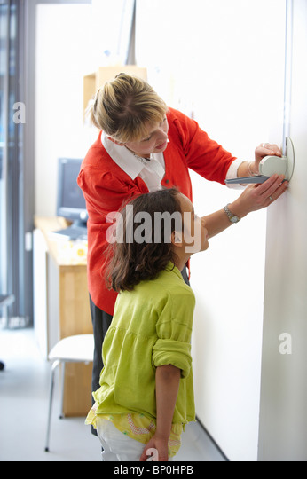 Doctor measuring height of young girl - Stock Image