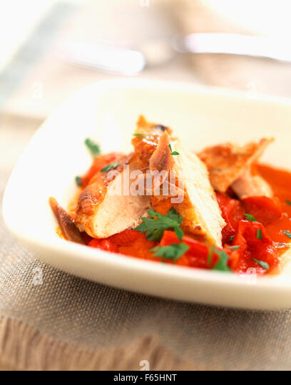 Thinly sliced chicken with peppers, tomatoes and anchovies - Stock Image
