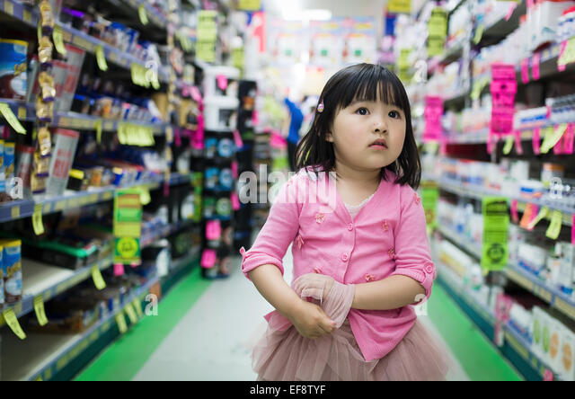 Front view of small girl walking alone between stalls in supermarket - Stock Image