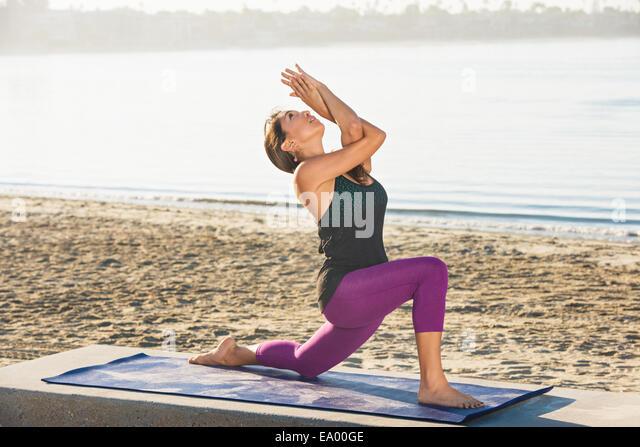 Young woman kneeling doing yoga on pier at Pacific beach, San Diego, California, USA - Stock-Bilder