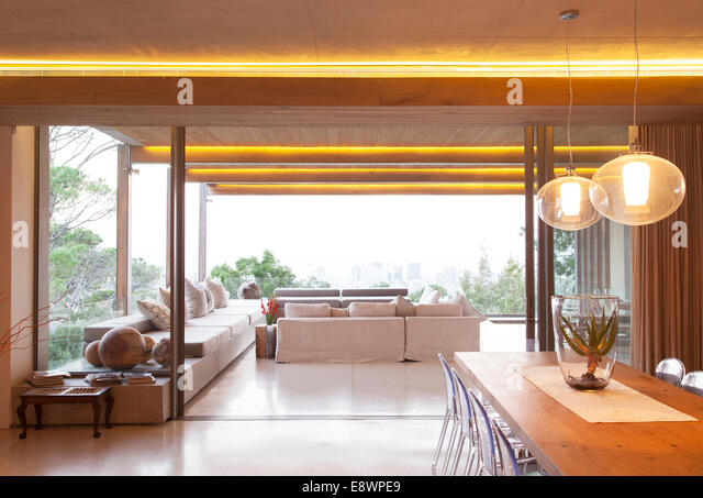 Sliding glass doors between open modern living and dining rooms - Stock Image