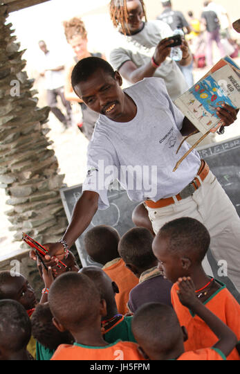 LOIYANGELENI, KENYA - May 18. A school teacher collects pencils after a writting lession at a school in the El Molo - Stock Image