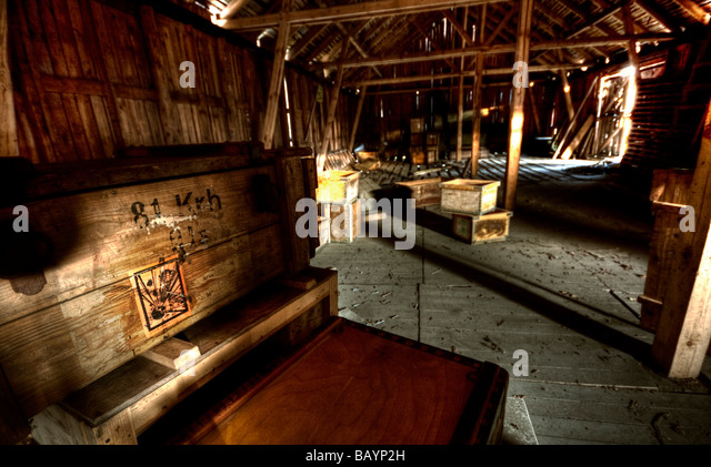 Crate with explosive warning sticker in wooden warehouse - Stock Image
