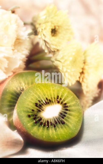 Still life of Kiwi fruit cut in half with background of white flowers - Stock Image