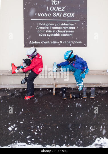 small boy and girl in ski clothing helmets and goggles sitting on a bench putting on ski boots with falling snow - Stock Image