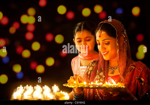 Mother holding a tray of diyas while her daughter looks on - Stock-Bilder