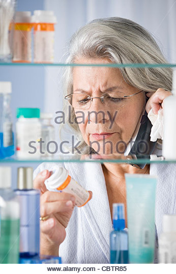 Hispanic woman talking on phone checking prescription - Stock Image
