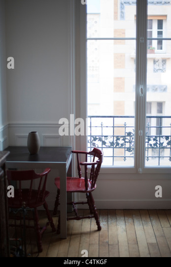 Table and chairs by window - Stock Image