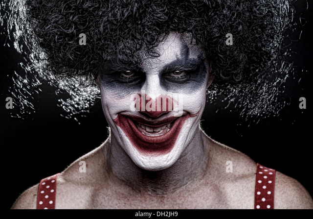 Evil Spooky Clown Portrait on Black Background - Stock Image