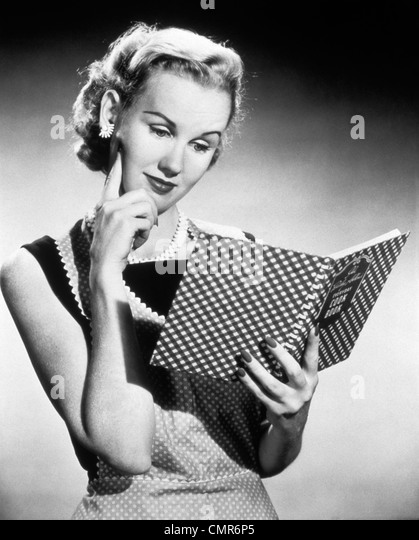 1950s THOUGHTFUL BLOND HOUSEWIFE READING COOK BOOK - Stock Image