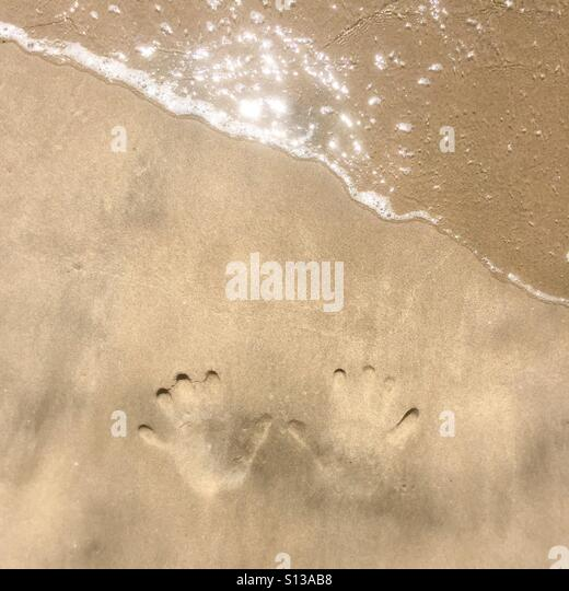 Hand prints in the sand at the beach. Manhattan Beach, California USA. - Stock Image