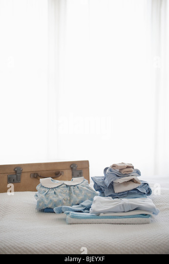 Childrens clothes folded on bed next to suitcase - Stock Image