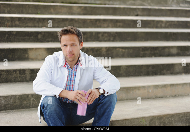 Man sitting on city steps - Stock Image