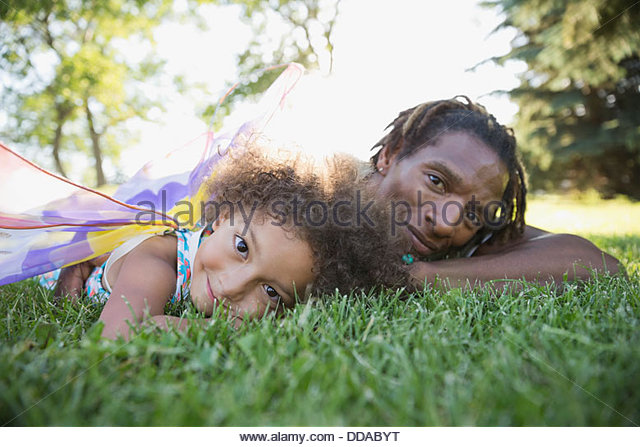 Father and daughter lying on grass - Stock-Bilder