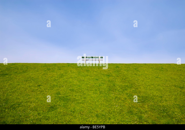 Solitary bench on a dike - Stock-Bilder