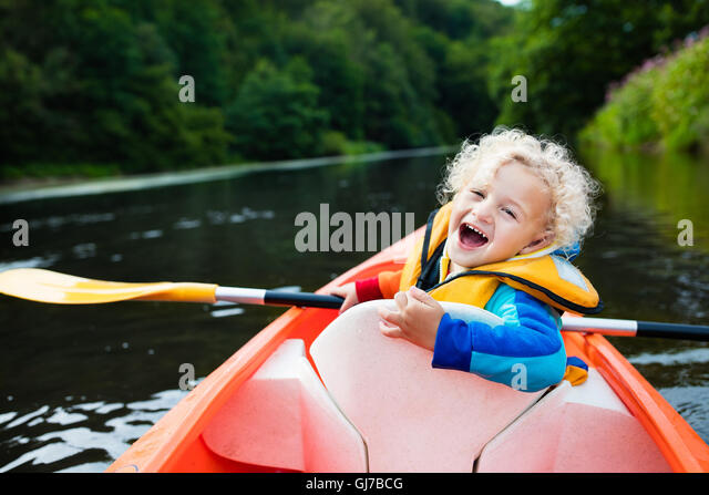 Happy kid enjoying kayak ride on beautiful river. Little curly toddler boy kayaking on hot summer day. Water sport - Stock Image