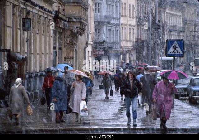 Ukraine L'vov L'viv buildings pedestrians residents coats umbrellas snow - Stock Image