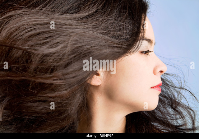 Woman's hair are being blown away in a swirling wind - Stock Image