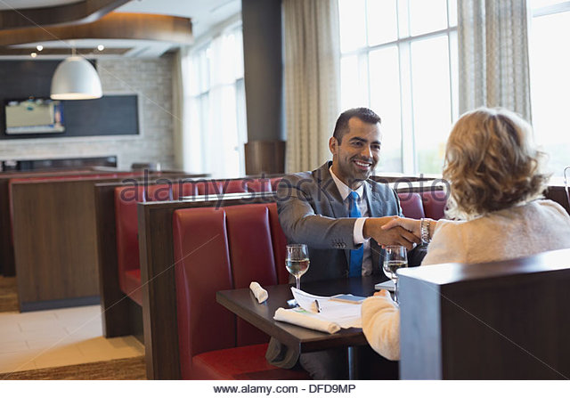 Business people shaking hands at hotel restaurant table - Stock Image