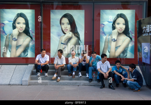 Male shoppers socialising under billboards on East Nanjing Road. Shanghai. China. - Stock Image