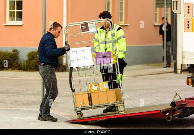 Trelleborg, Sweden - April 12, 2016: Two men are delivering a wire mesh rolling cart with merchandize from the back - Stock Image
