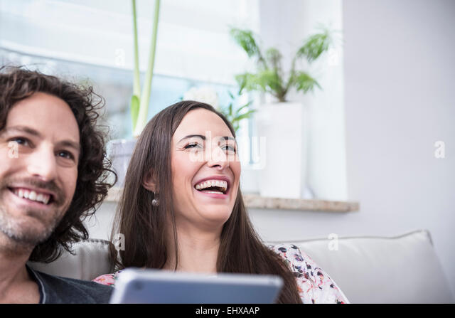 Couple laughing on couch with using digital tablet, Munich, Bavaria, Germany - Stock-Bilder