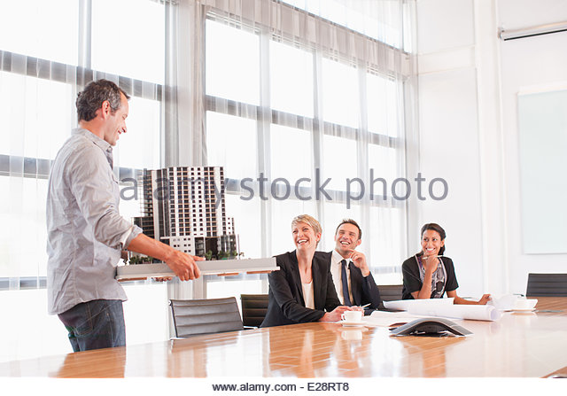 Business people looking at model building - Stock Image