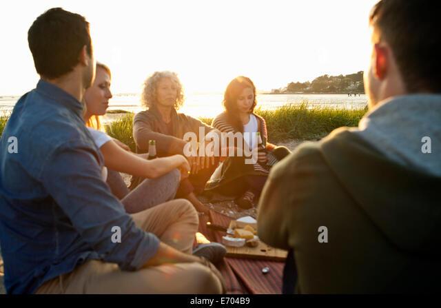 Five adult friends having picnic on Bournemouth beach, Dorset, UK - Stock Image