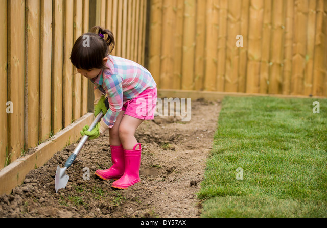 Young girl digging in the garden - Stock Image
