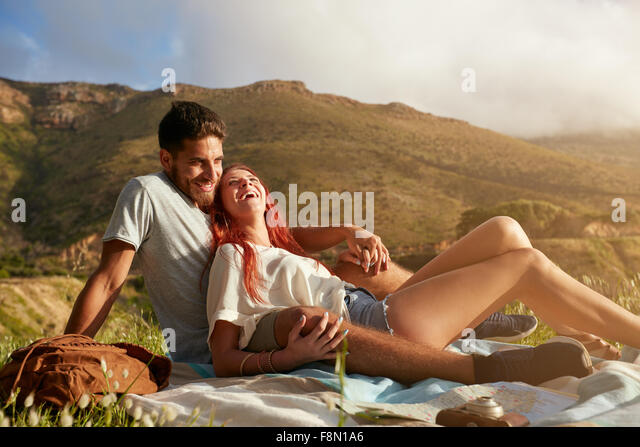 Portrait of a cute young couple sitting together and smiling. Young man and woman ion summer vacation. Enjoying - Stock-Bilder