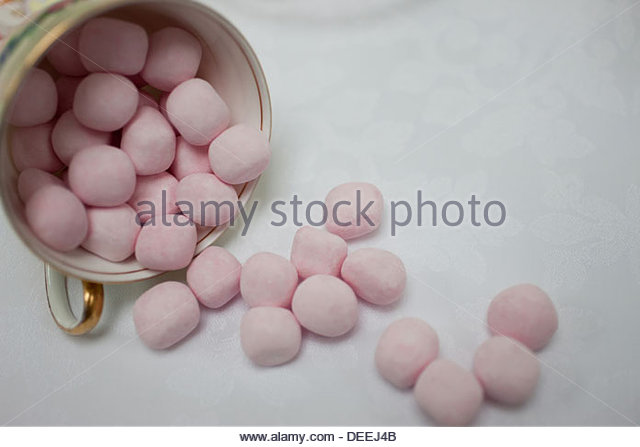 Sweets spilling out of coffee cup - Stock Image