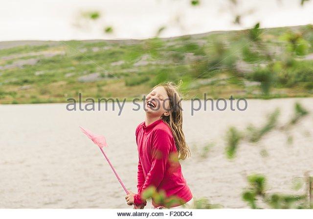 Girl with fishing net laughing at lakeside, Thingvellir, Iceland - Stock Image