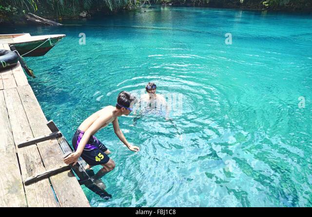Two boys swimming in Labuan Cermin Lake - Stock Image