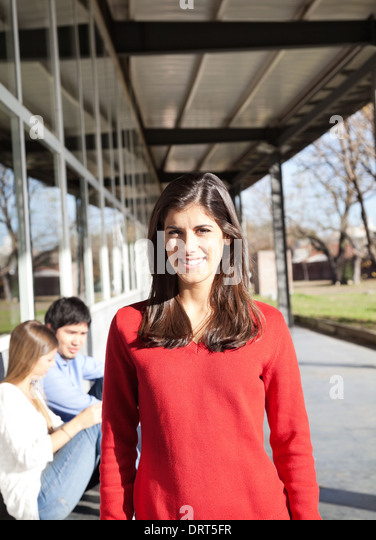 Woman Smiling With Students In Background On Campus - Stock Image