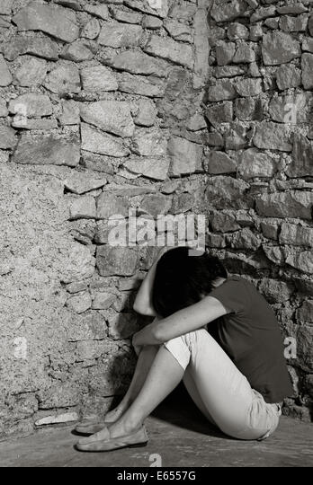 Depressed middle-aged woman sitting with head in hands in a room corner - Stock Image