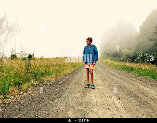 An eleven year old boy walking down a country track on a foggy day - Stock Image