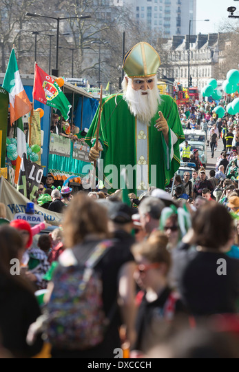 A 5m-tall St Patrick created by Emergency Exit Arts winds its way down the parade. St Patrick's Day Parade in - Stock Image