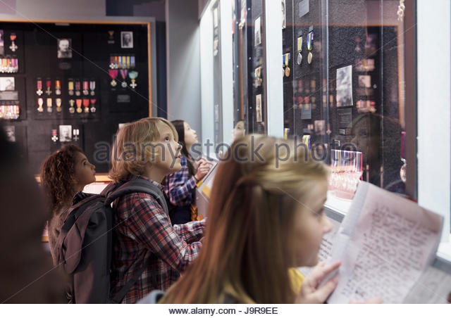 Curious students taking notes at exhibit on field trip in war museum - Stock-Bilder