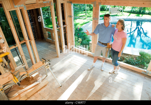 Mature couple standing construction frame home extension - Stock Image